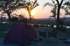 Располагаясь лагерем шатер, стулья и оснащение для кемпинга Восход солнца над граница рекой Okavango, Намибией Ботсваной Путешест Стоковая Фотография RF
