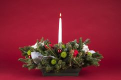 Расположение или Centerpiece таблицы рождества с цветками, вечнозелеными ветвями и белой свечой Lit Стоковое фото RF