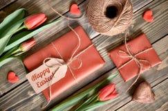 Расположение пасхи: красные тюльпаны, обернутые подарки, шнур и decorati Стоковое фото RF