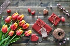 Расположение пасхи: красные тюльпаны, обернутые подарки, шнур и decorati Стоковое Изображение RF