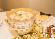 Расположение пудинга банана на белизне и партии золота тематической Стоковые Фотографии RF
