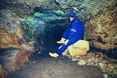 Расположите инженера подрядчика в голубых overal, резиновых ботинках и защитного шлема в подземно-минном тоннеле Стоковое Изображение