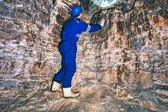 Расположите инженера подрядчика в голубых overal, резиновых ботинках и защитного шлема в подземно-минном тоннеле Стоковое Изображение RF