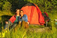 Располагаясь лагерем пары сидя и наслаждаясь заход солнца Стоковые Изображения