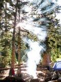 Располагаясь лагерем дым от лагерного костера с солнечным светом шатров Стоковая Фотография