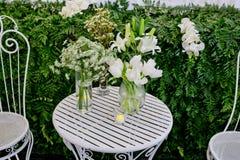Расположение белых цветков в стеклянных вазах на столе белого металла Стоковое фото RF