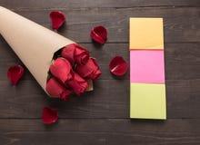 Расположение красных роз цветет с липкими примечаниями на деревянной предпосылке Стоковое Изображение
