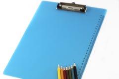 Расположение красочных карандашей и доски сзажимом для бумаги Стоковые Фото