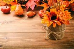 Расположение осени - бак с искусственными солнцецветом и тыквами на деревянной предпосылке Стоковое фото RF