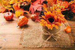 Расположение осени - бак с искусственными солнцецветом, конусами и листьями на деревянной предпосылке Стоковое Изображение