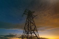 Распределение передачи и дальнего расстояния концепции электричества Двинутый под углом взгляд высоковольтной башни с линиями эле стоковые изображения rf