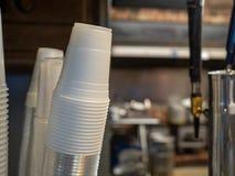 Распределитель бумажного стаканчика полагаясь для того чтобы выпрямить на баре, праве космоса экземпляра стоковое фото rf