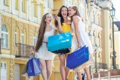 РАСПРОДАЖА! Девушки держа хозяйственные сумки и прогулку вокруг магазинов Smi Стоковое Фото