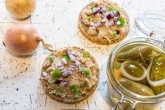 Распространение свинины, шпик и кислые огурцы на свежем круглом хлебе, взбрызнутом с весной и красным луком стоковые изображения rf