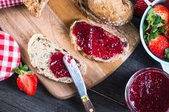 Распространяя варенье клубники на хлебе Стоковое Изображение RF
