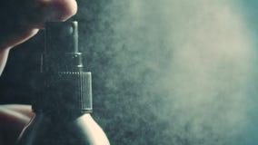 Распыляя вода или духи против темной предпосылки, супер замедленного  сток-видео