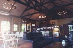 Расплывчатая предпосылка кофейни в темном тоне света Стоковые Фото