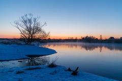 Рассвет зимы начиная над туманным рекой стоковые изображения