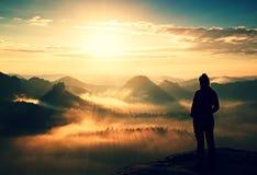 Рассвет осени пиршества одной маленькой девочки туристский на остром угле утеса и вахты песчаника над туманной долиной к Солнцю Стоковое Изображение