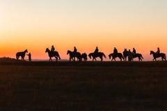 Рассвет лошадей Silhouetted всадниками Стоковое Изображение