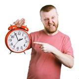 Рассерженный человек держа большой будильник стоковое фото rf
