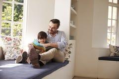 Рассказ чтения отца и сына дома совместно стоковое изображение