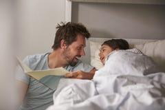 Рассказ чтения отца к дочери на времени ложиться спать стоковое изображение
