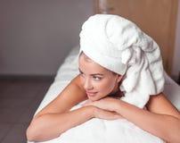 Расслабленная внушительная девушка с полотенцем на ее голове отдыхая после обработки стоковое фото