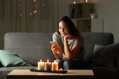 Расслабленная девушка используя телефон в ноче с свечой освещает стоковая фотография rf