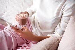 Расслабленная девушка используя smartphone дома Стоковые Фото
