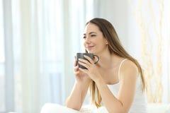 Расслабленная девушка просыпая вверх имеющ завтрак на кровати стоковая фотография