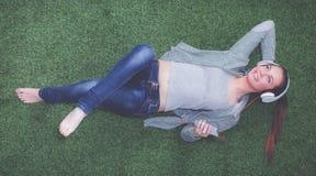 Расслабленная женщина слушая к музыке при наушники лежа на траве Стоковое Изображение
