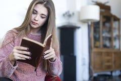 Расслабленная женщина читая книгу на софе дома стоковые изображения rf