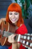 Расслабленная женщина redhaid играя гитару Стоковое фото RF