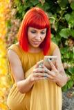 Расслабленная красная с волосами женщина с чернью в парке Стоковые Изображения RF