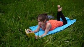 Расслабленная маленькая девочка читая книгу в поле Милый предназначенный для подростков лежать на траве Стрельба видео HD static видеоматериал