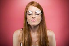 Расслабленная молодая женщина закрывая ее глаза пока ослабляющ над розовой предпосылкой стоковые фотографии rf