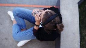 Расслабленная молодая женщина сидя на поле outdoors и слушая к музыке Нося голубые джинсы, белая футболка и сток-видео