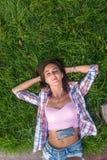 Расслабленная молодая женщина с наушниками слушая к музыке от smartphone и лежа на траве она глаза закрыло Стоковое фото RF