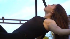 Расслабленное брюнет пошатывая в кольце для воздушной акробатики, замедленном движении сток-видео