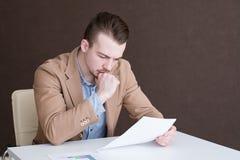 Расслабленное чтение коммерческого директора завертывает офис в бумагу стоковое фото