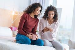 Расслабленные молодые дамы смотря smartphone пока сидящ на кровати Стоковая Фотография