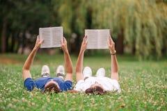Расслабленные молодые книги чтения пар пока лежащ на траве стоковые фото