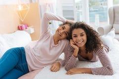 Расслабленные сестры лежа на кровати и испуская лучи совместно Стоковая Фотография RF