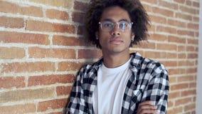 Расслабленный Афро-американский молодой человек смотря камеру пока полагающся на каменной стене дома акции видеоматериалы
