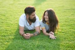 Расслабленный и в любов Пары ослабляя на траве наслаждаясь одином другого Хипстер человека бородатый и милая женщина в любов o стоковые изображения rf