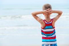 Расслабленный мальчик в футболке смотрит на море Стоковая Фотография