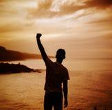 Расслабленный, победоносный человек наблюдая заход солнца Стоковые Изображения RF
