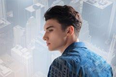 Расслабленный подросток смотря отсутствующий пока стоящ против предпосылки города Стоковые Изображения RF