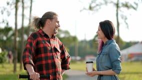 Расслабленный привлекательный средн-достигший возраста человек с длинными серыми волосами на пинк-скутере и молодая женщина с пок видеоматериал